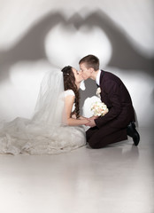 Newly married couple kissing while standing on knees