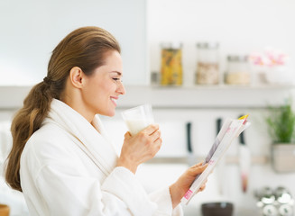 Happy housewife in bathrobe drinking milk and reading magazine