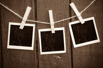 Photo paper attach to rope with clothes pins on wooden backgroun