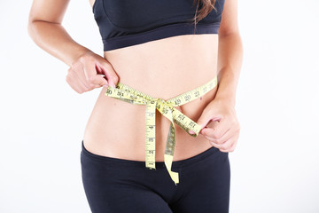 Slim girl with centimeter on light background