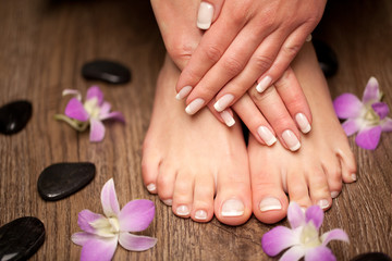 Foto op Plexiglas Manicure Relaxing pink manicure and pedicure with a orchid flower