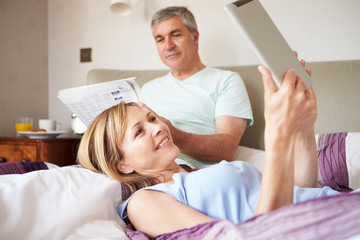 Couple Relaxing In Bed With Newspaper And Digital Tablet