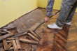 Renovation worker demolish oak parquet with crowbar tool