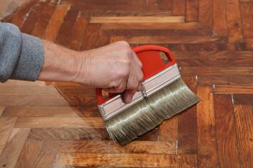 Obraz Varnishing of oak parquet floor, workers hand, brush - fototapety do salonu