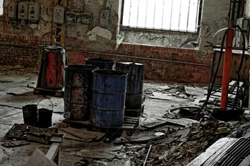 Damaged oil drums in industrial interior