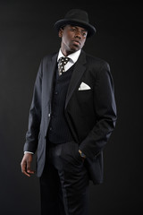 Retro african american gangster wearing striped suit and tie and