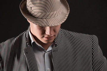 The man in style Chicago gangster on dark background