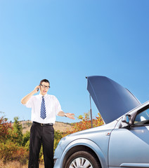 Young businessman standing near a broken car and talking on a mo