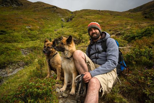 Lachender Mann mit Hunden in den Bergen