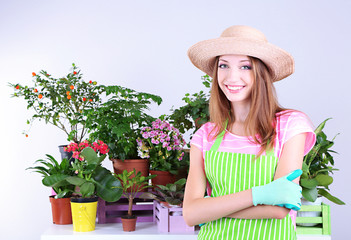 Beautiful girl gardener with flowers on grey background