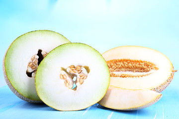 Ripe melons on wooden table on blue background