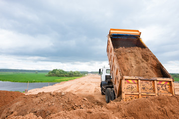 Dump truck unloading soil during road works