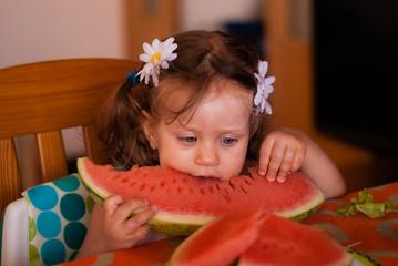 The baby girl eats watermelon