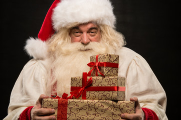 Santa Claus carrying big stack of Christmas gifts