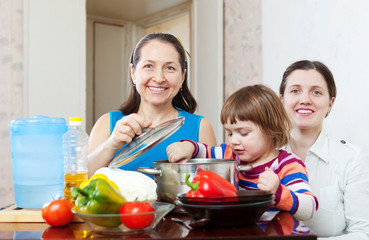 Happy women  with child together cooking veggie lunch
