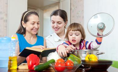 Happy women  cook vegetables in  kitchen