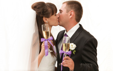 Married couple kissing and holding glasses of champagne