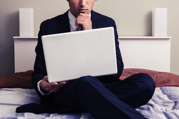 Serious young businessman working on laptop in hotel room