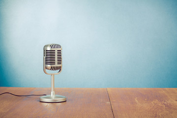 Retro style microphone on table in front aquamarine background