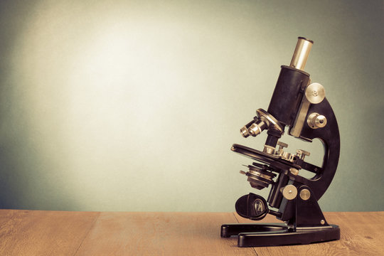Vintage microscope on table for science background