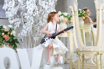 A little girl in white dress sings and plays guitar