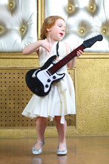 A small girl in white dress sings and plays guitar