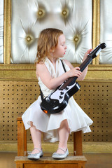 A small girl in white dress sitting in a chair with guitar
