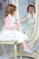 A little girl dressed admires her reflection in mirror