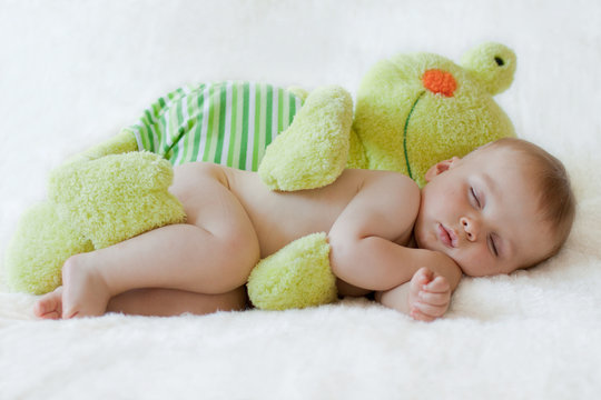 Baby boy, sleeping with a frog toy