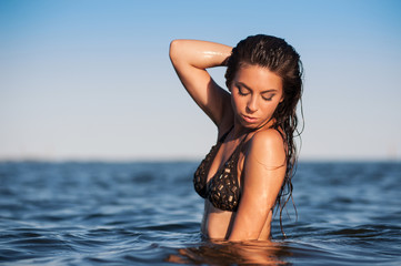 Sensual woman posing inside the water at the sea.