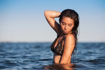 Sensual woman posing inside the water at the sea.