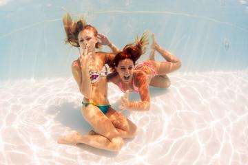 Two girls underwater portrait in swimming pool.