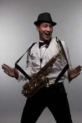 Portrait of happy and smiling saxophone player with hat.