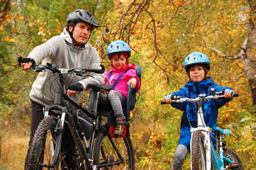Wall Murals Cycling Happy family on bikes in autumn park, having fun