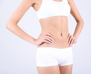 Beautiful woman stomach on  gray background