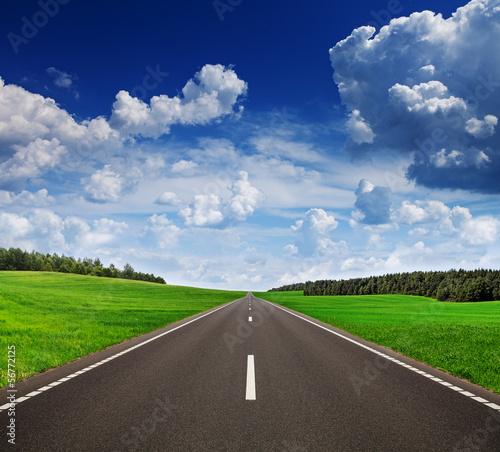Fototapete Asphalt road in green fields under beautiful sky