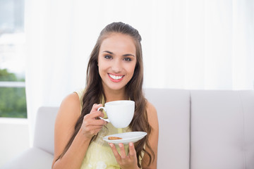 Smiling pretty brunette holding a cup