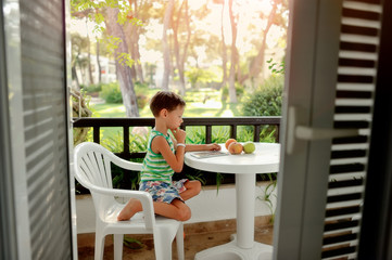 outside the window on a white chair sits a cute boy at a white t