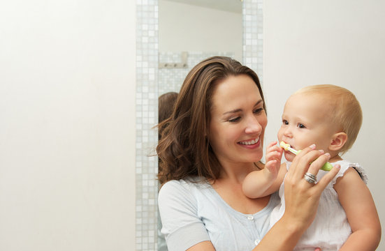 Mother teaching cute baby how to brush teeth with toothbrush