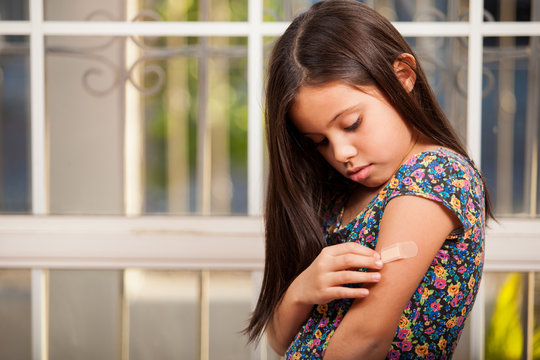 Little girl putting a band-aid on