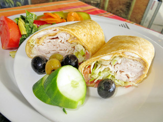 A turkey wrap with cucumbers and olives and a side salad