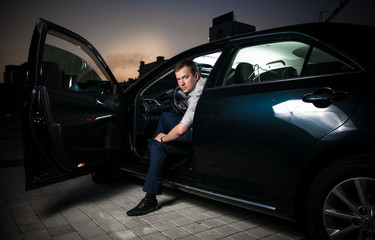 Sexy man sitting in car with front door open