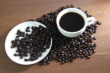 White coffee cup resting on coffee beans.