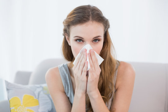 Sick young woman sitting on sofa blowing her nose