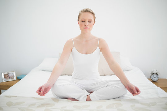 Natural pretty blonde meditating on bed with closed eyes