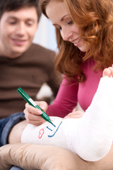 Girl is writting something on brocken leg bandage