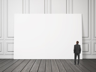 businessman looking at large blank poster