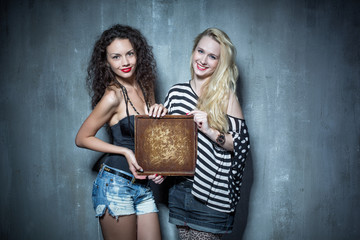 Two girls standing on the background of textured walls and show