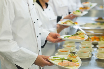 Chef holding salmon dishes