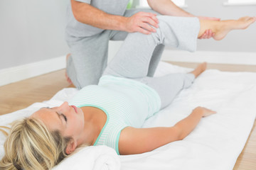 Physiotherapist checking patients leg on a mat on the floor